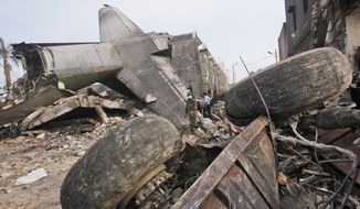 Rescuers search for victims at the site where an Indonesian Air Force cargo plane crashed in Medan, North Sumatra, Indonesia, Wednesday, July 1, 2015. The Hercules C-130 plane has crashed into a residential neighborhood in the country's third-largest city. (AP Photo/Binsar Bakkara)