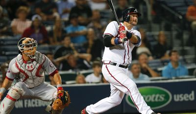 Atlanta Braves' A.J. Pierzynski (15) follows through on a two-run home run as Washington Nationals catcher Wilson Ramos (40) looks on in the fourth inning of Wednesday's game in Atlanta. (Associated Press)