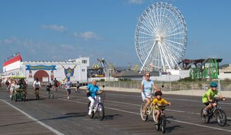 In this Aug. 29, 2012 photo, people ride bikes on the boardwalk in Ocean City, N.J. Ocean City was named New Jersey's most popular beach on Thursday July 2, 2015, marking the second year in a row and third time overall that the southern new Jersey resort won an online voting competition. (AP Photo/Wayne Parry)