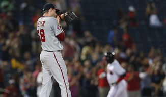 Washington Nationals starting pitcher Doug Fister (58) wipes his face as Atlanta Braves third baseman Juan Uribe (2) rounds the bases after hitting a home run in the fourth inning of a baseball game Wednesday, July 1, 2015, in Atlanta. Fister allowed two homer in the inning. (AP Photo/John Bazemore)
