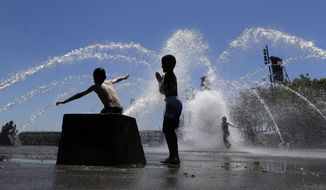 Children play in the Salmon Street Springs fountain in Portland, Ore., Wednesday, July 1, 2015. (AP Photo/Don Ryan) ** FILE **