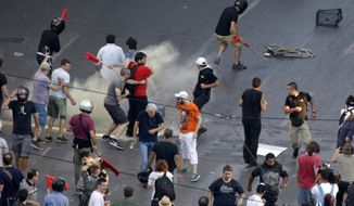 Riot police throw a tear gas canister as demonstrators run to avoid it before a rally organized by supporters of the No vote in Athens, Friday, July 3, 2015. Greeks will vote Sunday on whether to accept a proposal that creditors had made of specific reforms in exchange for loans. European Union institutions are framing it as a vote for or against the euro. (AP Photo/Thanassis Stavrakis)