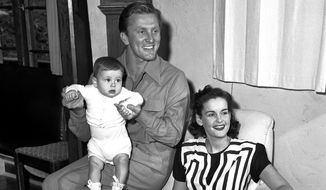 In this Sept. 9, 1947, file photo, actors Kirk and Diana Douglas pose with their second son, Joel, for his first portrait in the Hollywood district of Los Angeles. Diana Douglas, the first wife of Kirk Douglas and mother of Michael Douglas, has died in Los Angeles. She was 92. (AP Photo, File)
