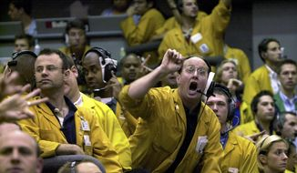 Clerks shout in the Euro Dollar Futures pit at the Chicago Mercantile Exchange in this Sept. 16, 2003, file photo. Most pits in Chicago and New York where traders bet on future prices of palladium and gold, cattle and corn and dozens of other commodities are expected to close for good on Monday, July 6, 2015. (AP Photo/Anne Ryan, File)