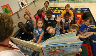 """In this file photo taken on Tuesday, June 30, 2015, Heidi Torrance, a teacher at Sunnyside Elementary School, reads """"On My Way to School"""" and interacts with students going into first grade during summer school at Grimes Elementary School in Burlington, Iowa. The class helps the students maintain the skill levels so they are prepared for school in the fall. The classes meet until August 10.  (John Gaines/The Hawk Eye via AP) MANDATORY CREDIT"""
