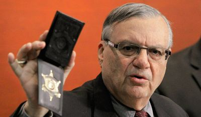 FILE- In this Dec. 21, 2011 file photo, Maricopa County Sheriff Joe Arpaio shows his badge as he holds a ceremony where 92 of his immigration jail officers, who lost their federal power to check whether inmates are in the county illegally, turn in their credentials after federal officials pulled the Sheriff's office immigration enforcement powers in Phoenix. The U.S. Justice Department is putting Arpaio on trial next month in a civil rights case that will focus in part on how the sheriff investigated and criminally charged people who crossed him from 2007 until 2010. (AP Photo/Ross D. Franklin, File)