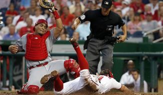 Washington Nationals' Matt den Dekker (21) scores as Cincinnati Reds catcher Brayan Pena, left, can't make the tag in time, after a wild pitch, during the third inning of a baseball game at Nationals Park, Monday, July 6, 2015, in Washington. (AP Photo/Alex Brandon)