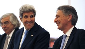 U.S. Secretary of State John Kerry, left, talks with British Foreign Secretary Philip Hammond, right, as they meet with foreign ministers from China, Germany and France at an hotel in Vienna, Austria Monday, July 6, 2015. (Carlos Barria/Pool Photo via AP)