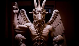This 2014 photo provided by The Satanic Temple shows a bronze Baphomet, which depicts Satan as a goat-headed figure surrounded by two children. (The Satanic Temple via AP)