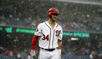 Washington Nationals' Bryce Harper (34) walks back to the dugout as the game is delayed due to rain during the first inning of a baseball game against the Cincinnati Reds at Nationals Park, Monday, July 6, 2015, in Washington. (AP Photo/Alex Brandon)