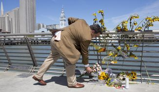 A mourner lays down flowers following a vigil for Kathryn Steinle, Monday, July 6, 2015, on Pier 14 in San Francisco. Steinle was gunned down while out for an evening stroll at Pier 14 with her father and a family friend on Wednesday, July 1. (AP Photo/Beck Diefenbach)
