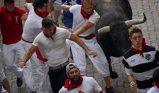 Revelers run with a Jandilla's ranch fighting bull during the running of the bulls of the San Fermin festival in Pamplona, Spain, Tuesday, July 7, 2015. Revelers from around the world turned out here to kick off the festival with a messy party in the Pamplona town square, one day before the first of eight days of the running of the bulls. (AP Photo/Daniel Ochoa de Olza)