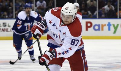 Washington Capitals left wing Liam O'Brien (87) shoots the puck in the first period of an NHL hockey game against the New York Islanders at Nassau Coliseum on Wednesday, Nov. 26, 2014, in Uniondale, N.Y. (AP Photo/Kathy Kmonicek)