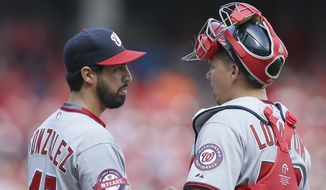 Washington Nationals starting pitcher Gio Gonzalez (47) and catcher Jose Lobaton (59) meet on the mound in the second inning of a baseball game against the Cincinnati Reds, Saturday, May 30, 2015, in Cincinnati. The Reds won 8-5. (AP Photo/John Minchillo)