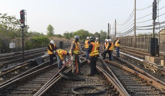 In this May 27, 2015, file photo provided by the Metropolitan Transit Authority, workers repair a section of cable that was severed by vandals who stole 500 feet of copper cable from train tracks along the A train subway line south of Howard Beach, in the Queens borough of New York. (Metropolitan Transit Authority, Marc A. Hermann via AP, File)