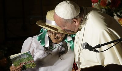 Pope Francis hugs Imelda Caicedo, a delegate of the Ecuadorian coastal farmers association, after she delivered a speech during his visit to the San Francisco Church in Quito, Ecuador, Tuesday, July 7, 2015. Francis is making his first visit as pope to his Spanish-speaking neighborhood. He travels to three South American nations, Ecuador, Bolivia and Paraguay. (AP Photo/Gregorio Borgia)