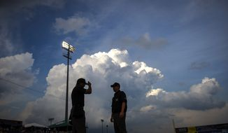 With storm clouds looming in the distance, umpires Erich Bacchus, left, and Chase Eade chat near the plate prior to the game, as the Frederick Keys host the Wilmington Blue Rocks at Nymeo Field at Harry Grove Stadium in Frederick, Md., Saturday, June 20, 2015. (Rod Lamkey Jr./Special for The Washington Times)