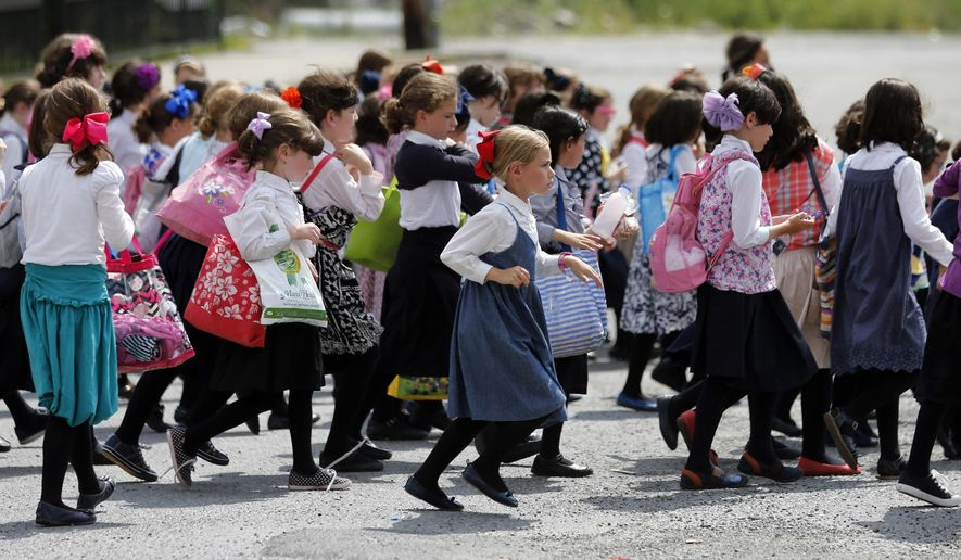 FILE - In this July 1, 2014, file photo, girls walk to ...