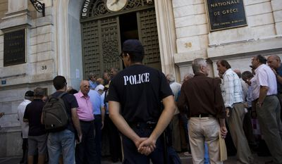 A police officer stands as pensioners wait outside the main gate of the national bank of Greece to withdraw a maximum of 120 euros ($134) in central Athens, Thursday, July 9, 2015. (AP Photo/Emilio Morenatti)