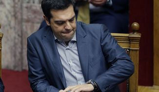 Greece's Prime Minister Alexis Tsipras looks at his watch during a parliament meeting in Athens, Friday, July 10, 2015. Lawmakers have been summoned to emergency sessions in parliament after Prime Minister Alexis Tsipras sought authorization to negotiate a new bailout deal with European creditors. (AP Photo/Thanassis Stavrakis)