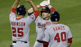 Washington Nationals' Danny Espinosa, center, high-fives teammates Clint Robinson, left, and Wilson Ramos after batting them in on a home run in the sixth inning of an interleague baseball game against the Baltimore Orioles, Saturday, July 11, 2015, in Baltimore. (AP Photo/Patrick Semansky)