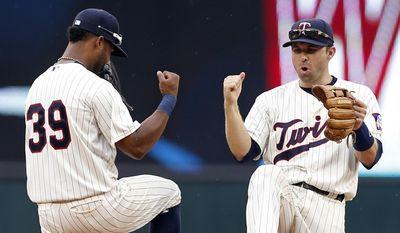 Minnesota Twins shortstop Danny Santana, left, and second baseman Brian Dozier celebrate their 9-5 win over the Detroit Tigers in a baseball game, Saturday, July 11, 2015, in Minneapolis. (AP Photo/Jim Mone)