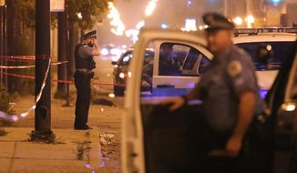 FILE - In this July 6, 2015, file photo, a Chicago police officer rests his hand on his forehead at the scene where a man was shot in the face in Chicago. Homicides and shooting incidents in Chicago are up roughly 20 percent from the same period last year.  (Anthony Souffle/Chicago Tribune via AP, File)
