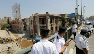 Egyptian police officers stand on the 6th October bridge opposite the Italian consulate following a blast in Cairo, Egypt, Saturday, July 11, 2015. A large explosion struck outside the Italian Consulate in Egypt's capital Cairo early Saturday, severely damaging the building and killing one civilian, and injuring four others, officials said. An Italian diplomat said the consulate was closed at the time and no staff members were wounded in the blast. (AP Photo/Amr Nabil) ** FILE **