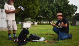 Walter Skold, right, founder of the Dead Poets Society of America, visits the final resting place of notable poet, jazz musician and philosopher Sun Ra at Elmwood cemetery in Birmingham, Ala., Friday, July 10, 2015.  The visit marked the 500th grave of a dead poet he has visited since starting his literary journey six years ago. Craig Legg, a Sun Ra fan from Birmingham, reads his poetry aloud. (Tamika Moore/AL.com via AP) MAGS OUT; MANDATORY CREDIT