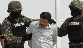 "In this Feb. 22, 2014, file photo, Joaquin ""El Chapo"" Guzman is escorted to a helicopter in handcuffs by Mexican navy marines at a navy hanger in Mexico City. (AP Photo/Marco Ugarte) ** FILE **"