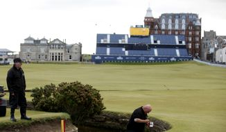 Greenkeepers paint the water hazard markers on the 18th hole at the Old Course, St Andrews, Scotland, Sunday, June 12, 2015. The 2015 Open Golf Championship that is due to take place at St. Andrews July 16-19.  (AP Photo/Peter Morrison)
