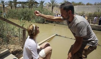 In this July 6, 2015 photo, a Christian visitor pours water from the Jordan River over the head of another at the baptismal area on the eastern bank of the river in South Shuna, Jordan, as people, background, gather for their baptism on the western bank at the Israeli-run site located in a part of the West Bank. UNESCO recently designated Jordan's baptismal area a World Heritage site, over the Israeli-run site of Qasr al-Yahud in the West Bank, which is one of three territories captured by Israel in the 1967 Mideast war. Qasr al-Yahud remains under full Israeli military occupation. (AP Photo/Raad Adayleh)