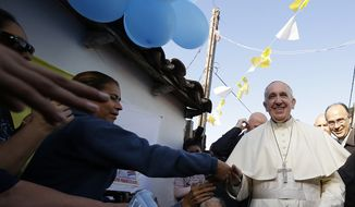 Pope Francis is greeted by the faithful during his visit to the Banado Norte neighborhood in Asuncion, Paraguay, Sunday, July 12, 2015. Pope Francis began the last day of a weeklong South American tour with a stop to the Asuncion slum that borders the Paraguay river that frequently floods it and makes its dirt roads impassable pools of mud. (AP Photo/Gregorio Borgia, Pool)