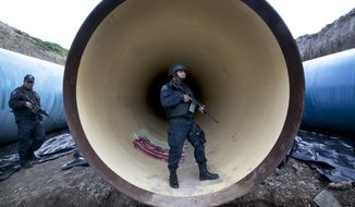Federal police guard a drainage pipe outside of the Altiplano maximum security prison in Almoloya, west of Mexico City, Sunday, July 12, 2015. (Associated Press)