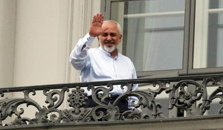 Iranian Foreign Minister Mohammad Javad Zarif waves to journalist from a balcony of the Palais Coburg where closed-door nuclear talks with Iran continue in Vienna, Austria, Monday, July 13, 2015. (AP Photo/Ronald Zak)