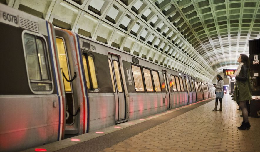 Passengers wait on the platform before boarding a train at the U Street Metro Station in Washington. (Associated Press) **FILE**