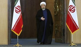 "Iran's President Hassan Rouhani arrives for an address to the nation after a nuclear agreement was announced in Vienna, in Tehran, Iran, Tuesday, July 14, 2015. Rouhani said ""a new chapter"" has begun in his nation's relations with the world. He maintained that Iran had never sought to build a bomb, an assertion the U.S. and its partners have long disputed. (AP Photo/Ebrahim Noroozi)"