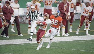 Washington Redskins wide receiver Ricky Sanders (83) is followed by Denver Broncos cornerback mark Haynes (36) as he goes into the endzone for a touchdown in the second quarter of Super Bowl XXII, Sunday, Jan. 31, 1988 in San Diego. Sanders, who set a record for most yardage in first half of a Super Bowl, scored on a pass from quarterback Doug Williams. (AP Photo/Reed Saxon)