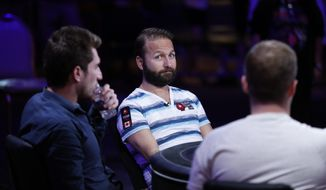 Daniel Negreanu, center, competes at the World Series of Poker main event Tuesday, July 14, 2015, in Las Vegas. (AP Photo/John Locher)