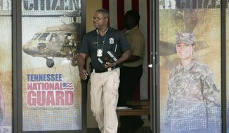 A police officer investigates outside the Armed Forces Career Center after a gunman opened fire on the building Thursday, July 16, 2015, in Chattanooga, Tenn. Authorities say there were multiple casualties including the gunman.   (AP Photo/John Bazemore)