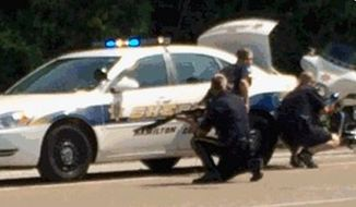 In this image made from video and released by WRCB-TV, authorities work an active shooting scene on amincola highway near the Naval Reserve Center, in Chattanooga, Tenn. on Thursday, July 16, 2015. Chattanooga Mayor Andy Berke says police are pursuing an active shooter after reports of a shooting at the military reserve center. (WRCB-TV via AP)