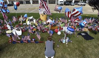 Daly Simmons, 26, sits as she prays in front of a makeshift memorial outside the Armed Forces Career Center Saturday, July 18, 2015, in Chattanooga, Tenn.    Muhammad Youssef Abdulazeez, of Hixson, Tenn., attacked two military facilities on Thursday, in a shooting rampage that killed four Marines and one U.S. Navy sailor.  (AP Photo/Mark Zaleski)