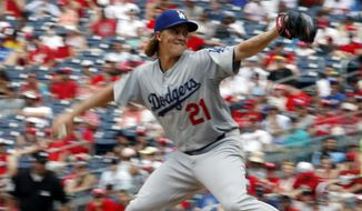 In this photo taken with a slow shutter speed, Los Angeles Dodgers starting pitcher Zack Greinke (21) throws during the fourth inning of a baseball game against the Washington Nationals at Nationals Park, Sunday, July 19, 2015, in Washington. (AP Photo/Alex Brandon)