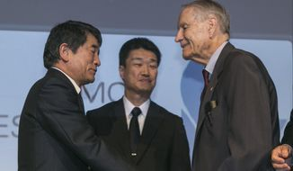 Yukio Okamoto (left), Outside Board Member of Mitsubishi Materials and former Special Advisor to Japan's Prime Minister, and Hikaru Kimura, Senior Executive Officer Mitsubishi Materials, offer an apology as they hold hands with 94-year-old U.S. prisoner of war James Murphy at the Simon Wiesenthal Center in Los Angeles on Sunday. (Associated Press)