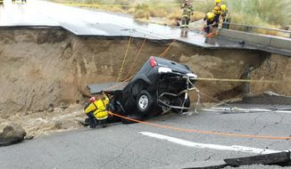 In this photo provided by the CAL FIRE/Riverside County Fire Department, emergency crews respond after a pickup truck crashed into the collapse of an elevated section of Interstate 10, Sunday, July 19, 2015, in Desert Center, Calif. (Chief Geoff Pemberton/CAL FIRE/Riverside County Fire via AP)
