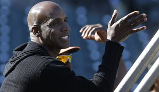 FILE - In this Friday, July 10, 2015, file photo, former baseball player Barry Bonds watches batting practice before a baseball game between the San Francisco Giants and the Philadelphia Phillies in San Francisco. The U.S. Department of Justice formally dropped its criminal prosecution of Barry Bonds, Major League Baseball's career home run leader. The decade-long investigation and prosecution of Bonds for obstruction of justice ended quietly Tuesday morning, July 21, 2015, when the DOJ said it would not challenge the reversal of his felony conviction to the U.S. Supreme Court.  (AP Photo/Jeff Chiu, File)