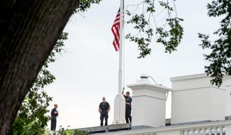 The American flag is lowered to half-staff above the White House in Washington, Tuesday, July 21, 2015, to honor the five U.S. service members who were killed by a gunman in Chattanooga, Tenn., last week. (AP Photo/Andrew Harnik)