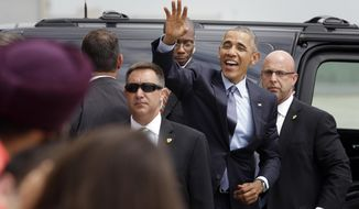 """President Obama waves to supporters as he leaves John. F. Kennedy International Airport. He was in New York on Tuesday for a taping of """"The Daily Show"""" and a private fundraiser. (AP Photo)"""