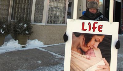 An abortion protester stands outside the Red River Women's Clinic in Fargo, N.D., on Feb. 20, 2013. (Associated Press)