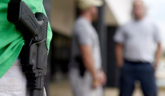 In this photo taken Monday, July 20, 2015, a man who would only give his name as J.R., from Norfolk, Va., stands with his sidearm as dozens of people, some armed with weapons and some carrying water, to the front door of the Armed Forces Career Center in Huntsville, Ala. Armed civilians patrolled the sidewalk and parking lot in front of the storefront recruiting center after five service members were killed by a lone assailant in Chattanooga, Tenn. (Eric Schultz/AL.com via AP)